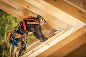 Wooden Roof Frame Construction Work. Caucasian Worker Finishing Wooden Skeleton Frame.construction I poster