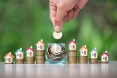 House On The Coin Ladder.in A Glass Jar Have Coins.the Hand Of A Business Person Is Going To Place A poster