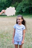 Pretty happy smiling thinking little girl posing summer nature outdoor with cloud of thoughts (like  poster