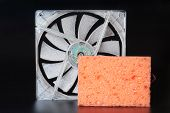 A Personal Computer Fan Is Covered With A Thick Layer Of Dust Next To A Bright Cleaning Sponge On A  poster
