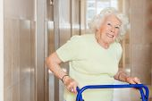 image of zimmer frame  - Portrait of a happy senior woman in hospital using Zimmer frame - JPG