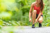 Fitness girl getting ready to run exercise outside lacing running shoes on run path in forest. Happy poster