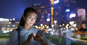 Woman look at cellphone at night in city poster