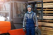 Young male worker standing next to the forklift in lumber yard   poster