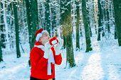 Santa Claus Blows Snow. Happy Santa Blowing On Snow. Winter Time. Photo Of Santa Claus Blowing Snow  poster