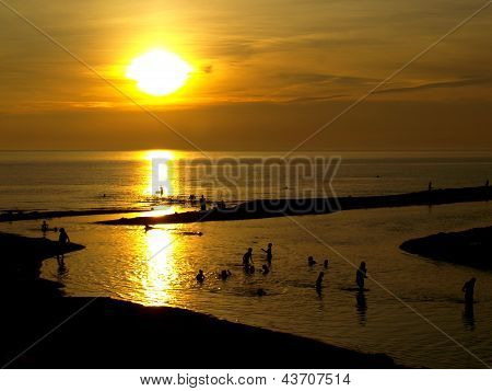 Swimmers at sunset on a Lake Michigan beach at Duck Lake State Park near Whitehall