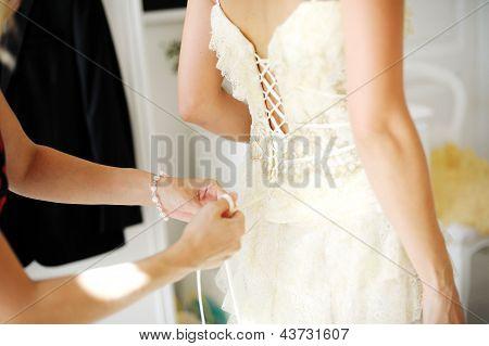 Bridesmaid Helping Bride To Dress