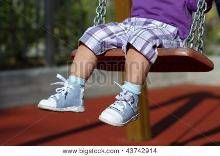Feet Of Unrecognizable Baby Swinging On Playground