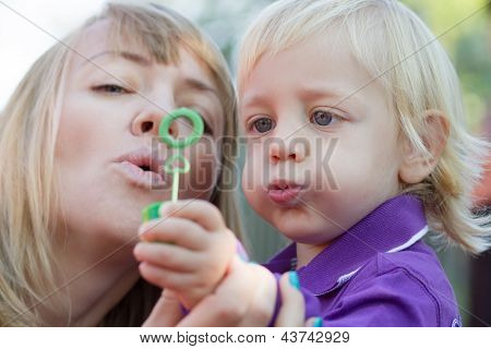 Mom And Her Baby Boy Blowing Bubbles