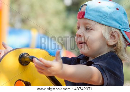 Cute Blond Boy On Playground