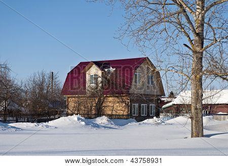 Wooden House With A Loft In Winter Time
