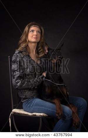 Woman with dobermann dog on black background