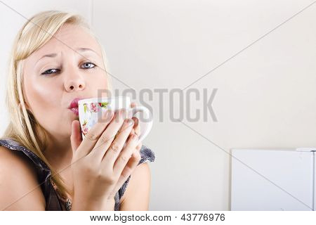 Portrait Of A Female Drinking Coffee In Kitchen