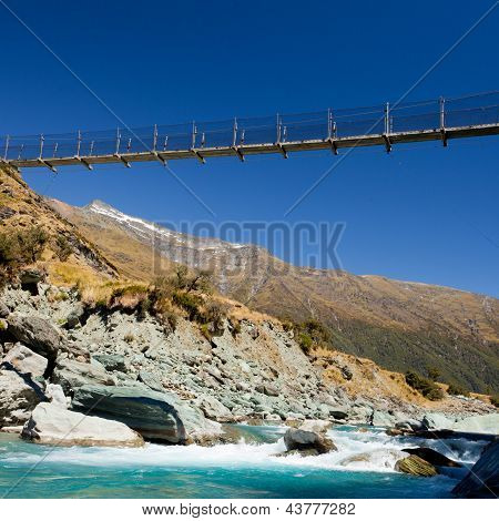 Swing bridge high over glacial river New Zealand