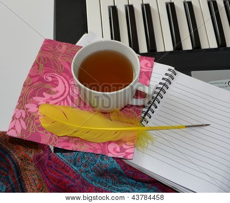 Still Life With A Cup Of Tea, A Notebook And A Feather Near Synthesizer