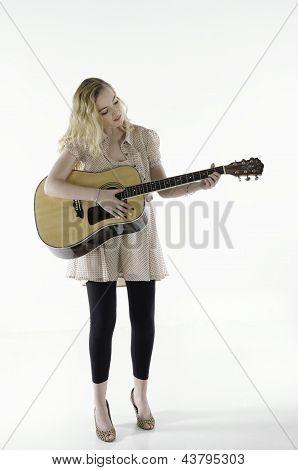 teenage girl playing guitar - full body