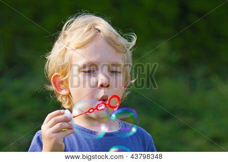 Blond Boy Making Soap Bubbles Outside