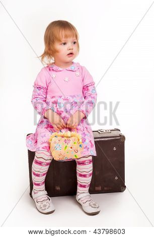 portrait of adorable young girl on old suitcase