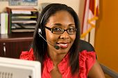 stock photo of receptionist  - A beautiful African American receptionist wearing a headset and glasses smiling as she looks toward the camera - JPG