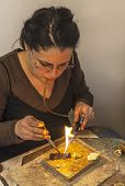 stock photo of blow torch  - Female jeweller blowing a torch to melt metal for making a brooch in her workshop.