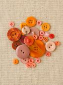 Pile Of Orange Buttons On Hessian