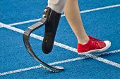 stock photo of amputation  - female athlete with handicap is crossing the line - JPG