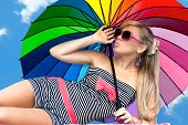 Glamorous Girl In Retro Style By Color Umbrella On The Beach