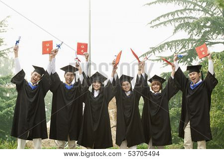 Young group of university graduates with diplomas in hand