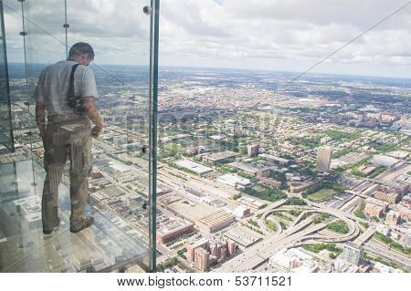 A Boy Looks Out From The Transparent Balcony Of Th Willis Tower