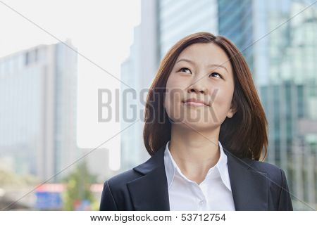Smiling young businesswoman looking away