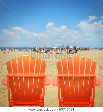 Two Orange Beach Chairs In Sand