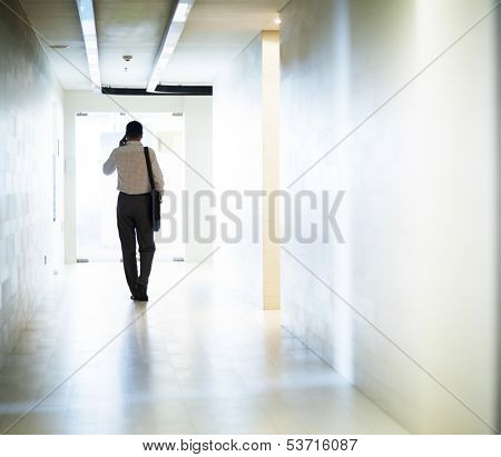 Businessman talking on phone and walking down the corridor