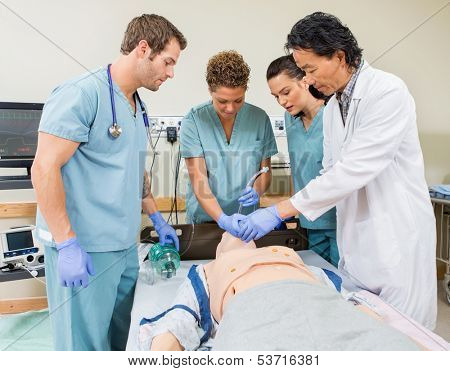 Male doctor instructing nurses to insert endotracheal tube in dummy patient's mouth in hospital room
