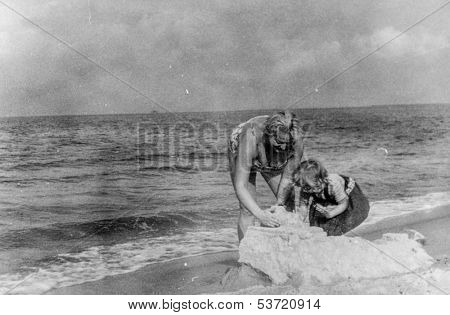 Vintage photo of mother and daughter playing on beach, fifties