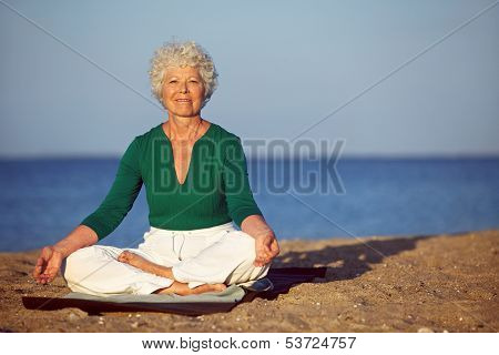 Senior Woman Meditating On Sandy Beach