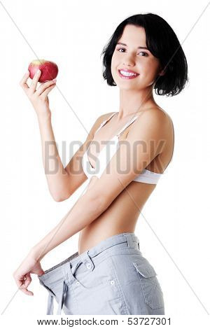 Attractive woman in baggy trousers with apple. Isolated on white.
