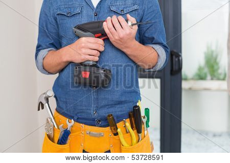Close up mid section of a handyman with drill and toolbelt