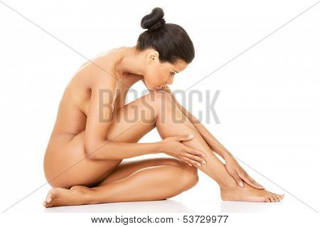 Attractive naked woman sitting. Side view. Isolated on while.