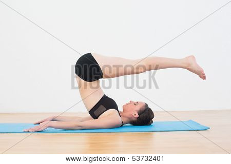 Full length side view of a fit young woman doing the plough posture in fitness studio