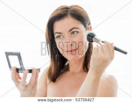 Woman in her forties applying makeup