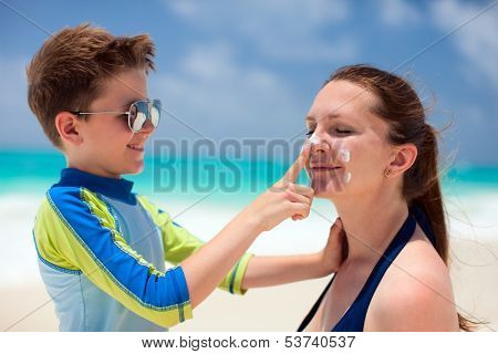 Little boy applying sun cream to her mother nose
