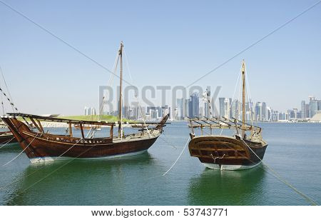Traditional wooden dhows moored off Museum Park, Doha, Qatar, with the city's postmodern 21st Century high-rise skyline beyond.