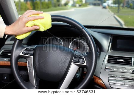 Hand with microfiber cloth cleaning car.