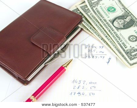 US dollars, notebook and pen