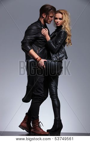 young sexy woman in leather jacket is pulling her man closer and looks at the camera