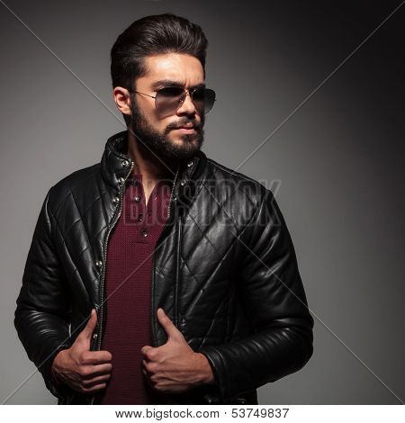 serious bad boy wearing leather jacket and sunglasses looking away to his side on gray background