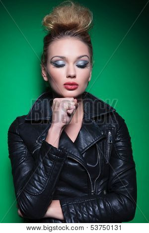 young pensive fashion woman with her fist closed, wearing a leather jacket on green background