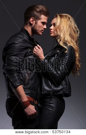 young fashion man and woman looking at each other while standing embraced on gray background