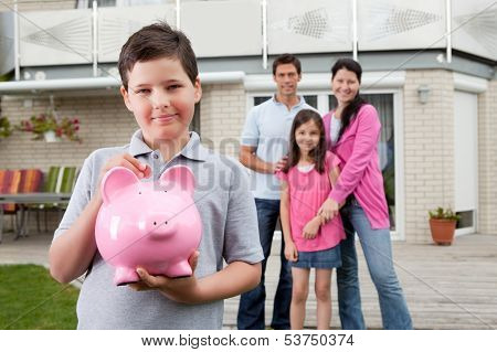 Small Boy Saving Money With Family At The Back