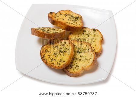 Garlic croutons drenched with herb butter isolated on white.